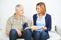 Frau bei Blutdruckmessung bei Patient