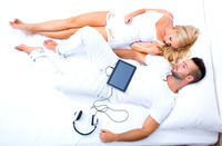 Beautiful young couple using a Tablet PC in Bed