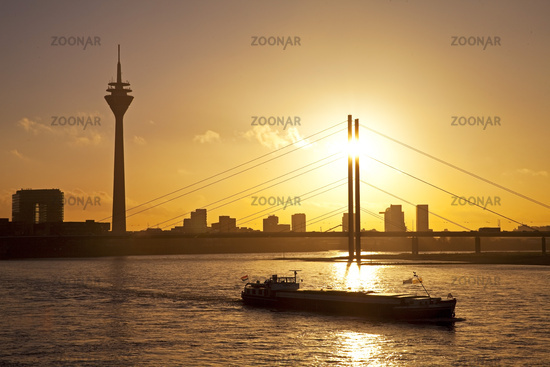 The Rhine with cargo ship, city gate, the Rhine Tower and the Rheinkniebruecke, Duesseldorf, Germany