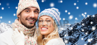 smiling couple in winter clothes over mountains