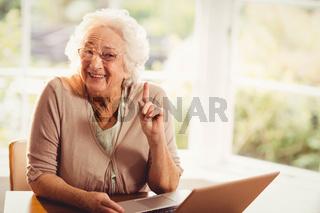 Smiling senior woman raising finger using laptop