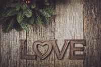 Love for Christmas Text with Pine Branches with Hollu Berries and Rustic Wood Background