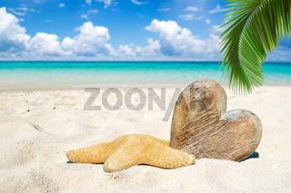 Herz aus Holz zum beschriften und ein Seestern liegen am Strand