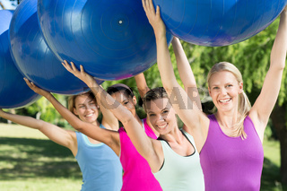 Fitness group holding exercise balls