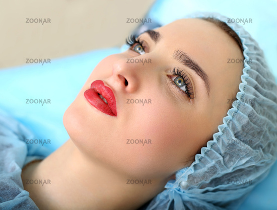 Cosmetologist making permanent makeup on woman#39;s face