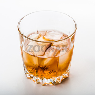 Glass of cold whiskey on white surface