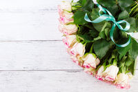 Bouquet of pink roses with blue ribbon for present on a vintage wooden background