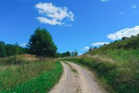 Beautiful summer landscape with road to forest, sky and clouds