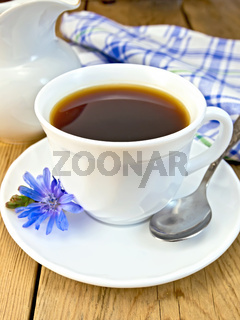 Chicory drink in white cup with spoon and milkman on board