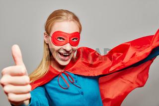 Frau als Superheld hält Daumen hoch
