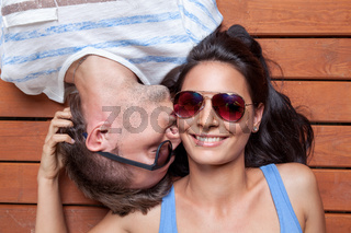 Happy young couple lying head to head on a wooden floor