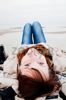 Smiling happy woman lying on the beach on a spring or autumn day