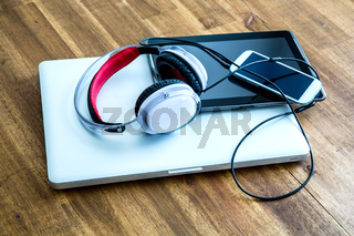 Digital devices and Headphones on a wooden Desktop