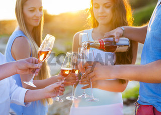 Happy friends pouring champagne sparkling wine into glasses outdoors at a beach