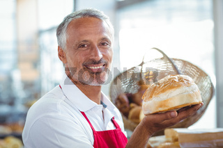 Waiter looking at camera and holding freshly baked bread