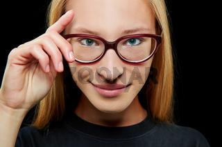 Lächelnde Frau mit Hand an der Brille