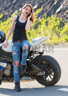 Girl calling on the phone near motorcycle.