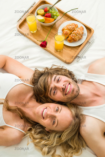 Cute couple lying in bed next to a breakfast tray