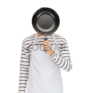 man or cook in apron hiding face behind frying pan