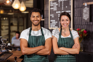 Smiling baristas standing with arms crossed