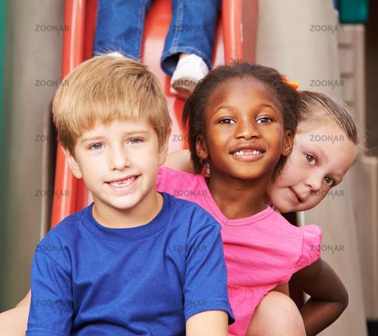 Gruppe Kinder sitzt hintereinander auf Rutsche