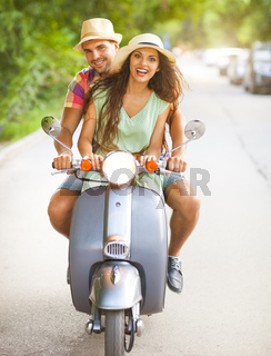 Happy young couple riding a vintage scooter in the street wearing hats