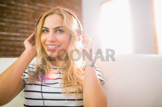 Pretty blonde listening to music on couch