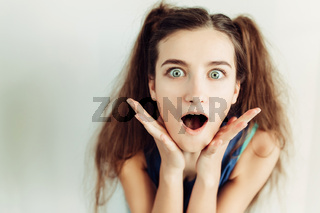 Surprised young girl with pigtails