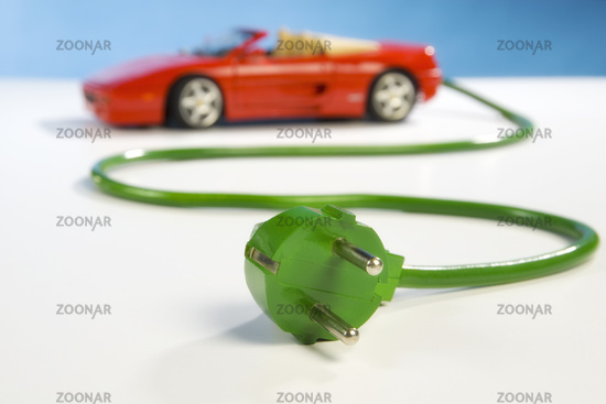 Red sport car with green power cable