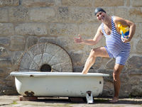 Man in retro swimsuit going to the bathtub outdoor