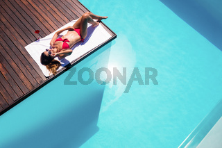 Woman enjoying sunbath on the pool edge