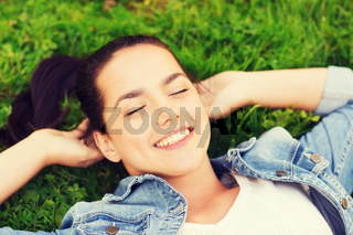 smiling young girl with closed eyes lying on grass