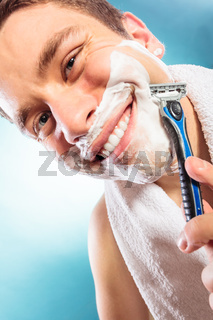 Happy man shaving using razor with cream foam.