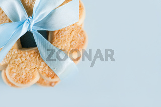 Cookies with blue ribbon on blue background, top view