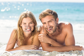 Happy couple relaxing together in the sand