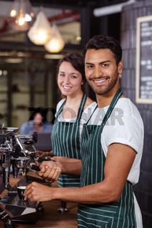 Smiling baristas using coffee machine