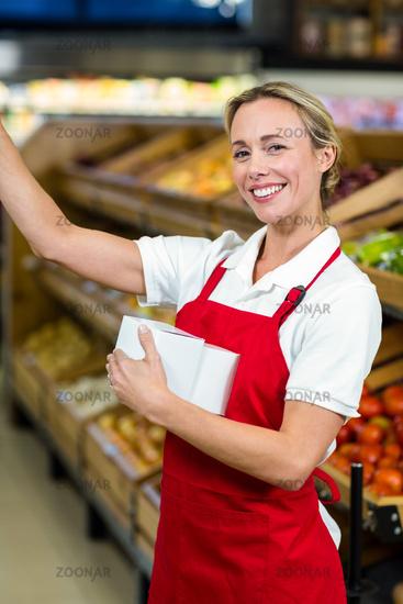 Smiling seller holding white plastic bag