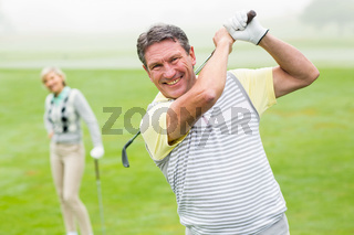 Happy golfer teeing off with partner behind him