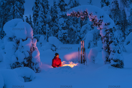 man beside a campfire in wintery landscape, Lapland, Sweden