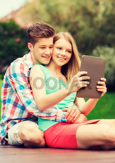 smiling couple with tablet pc making selfie