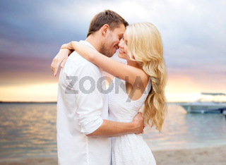 happy couple hugging over sunset at summer beach