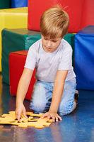 Kind spielt mit Puzzle im Kindergarten