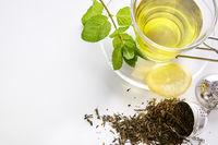 Green tea with mint lemon and metal strainer closeup top