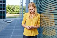 Studentin liest Nachricht auf ihrem Smartphone