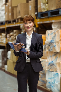 Smiling businesswoman scrolling on digital tablet