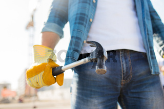 close up of builder hand in glove holding hammer