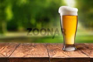 Beer in glass on wooden table against park