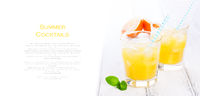 Summer yellow orange lemonade with ice and blood oranges and straw on a wooden table on a white background with place for text