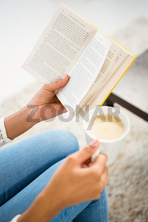 Close up view of woman holding cup of coffee and book