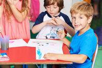 Junge malt Bild mit Wasserfarben im Kindergarten